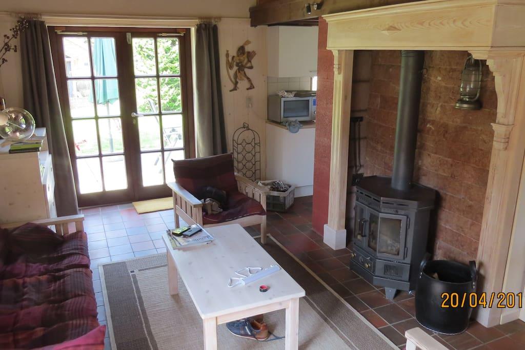 Woonkamer met houtkachel en openslaande deuren naar het terras
