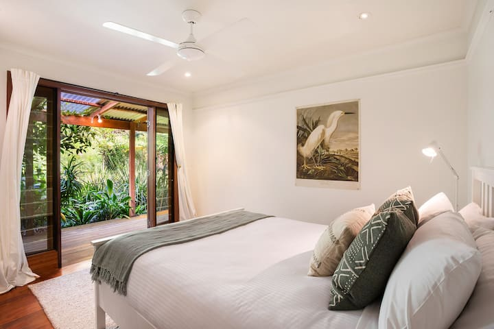 A secondary bedroom is furnished with a queen bed and black-out blinds, and has direct access to the outdoor deck