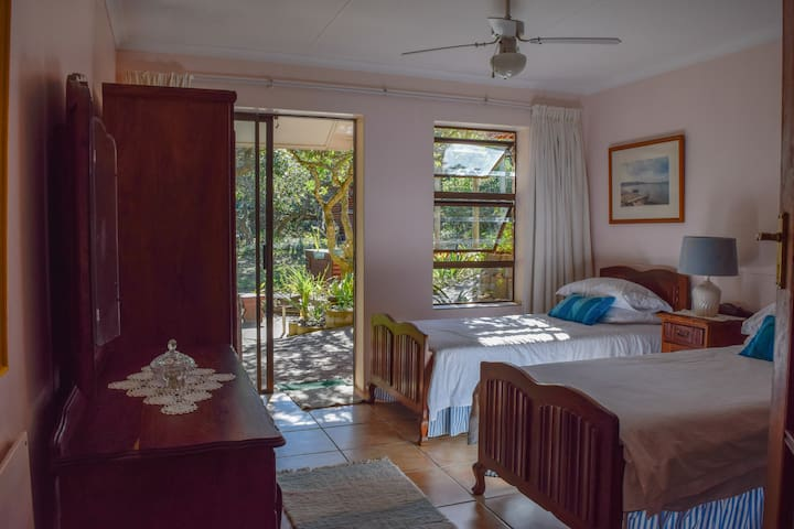 Bedroom 2 has two single beds, two wardrobes and a dressing table (beautiful Kiaat wood). It is next to the barbecue area under the milkwood trees. Both bedrooms have access to a covered patio. Two heated towel rails are available.