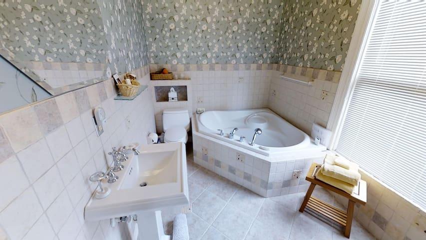 Bathroom has spa tub, separate shower