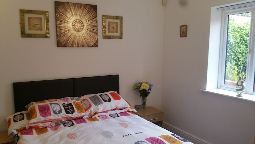 The bed has two bedside tables with bedside lamps available. This room has wall art to enhance this lovely space.