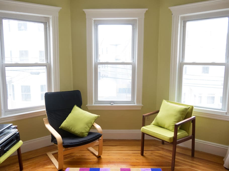 Sunny living room with bay windows.