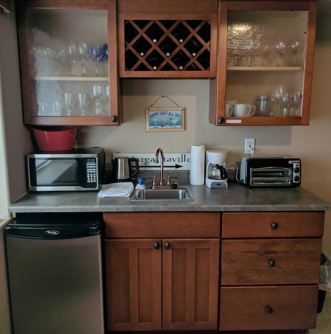Wet bar with mini fridge, toaster oven, microwave, and lots of breakfast items, snacks, and drinks
