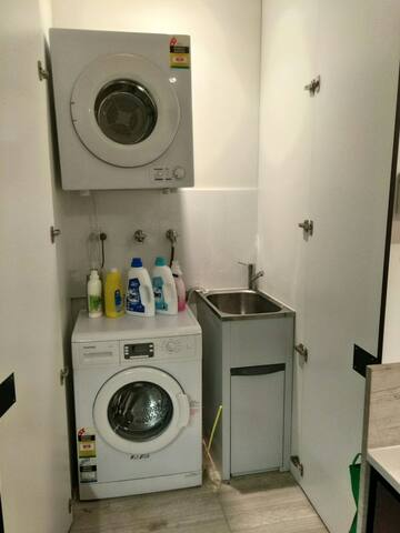 The Laundry Unit - with front loader washing machine and dryer. Includes laundry detergent, fabric softener, starch. Clothing iron and board also available for use.