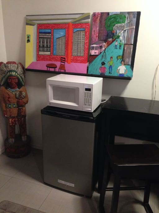 Microwave, Fridge, Dining Table w/ 2 tall chairs + lots of artwork.