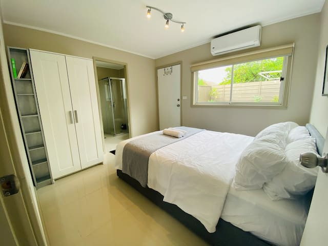 Bedroom with spacious wardrobe and full body mirror.