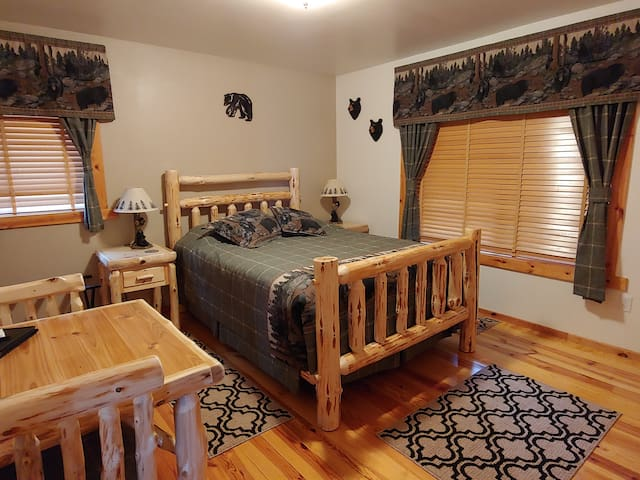 The cozy Black Bear room has a comfortable queen bed and sleeps two. There are luggage racks, a wardrobe, a Smart TV and a work table with two chairs plus high speed Wifi access.