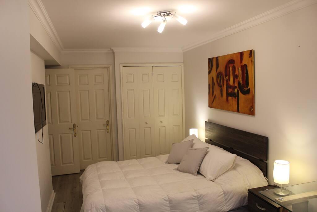 Dormitorio principal con cama matrimonial equipada con televisor HD, escritorio, lámparas, silla, cojines, etc.