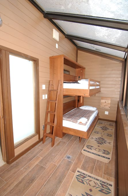 Sun room with single over single bunk bed, with views of forest.