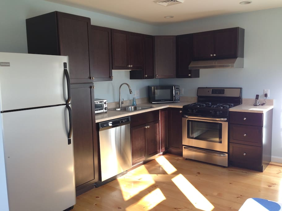 Modern kitchen with new appliances including full size fridge, dishwasher, gas stove, toaster, microwave, coffee maker