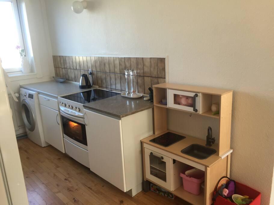 køkken med opvaskemaskine, vaskemaskine, ovn, stort køleskab m.m