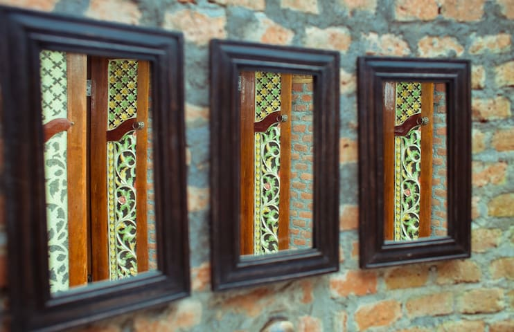 bathroom mirror view of the vintage Javanese wood carved door.