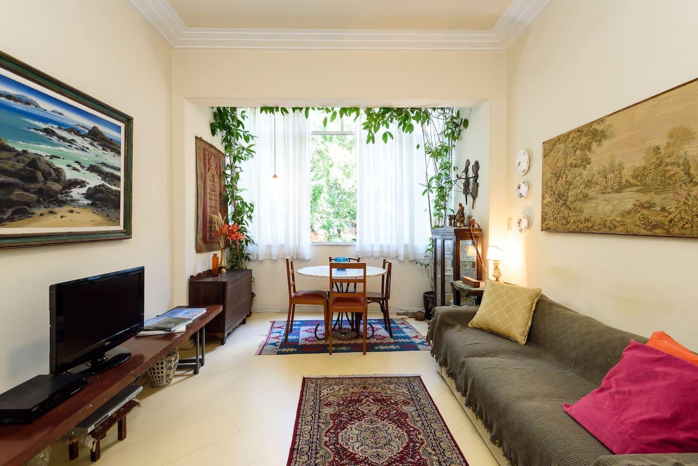 Sala com Tv a cabo, sofá e mesa de jantar