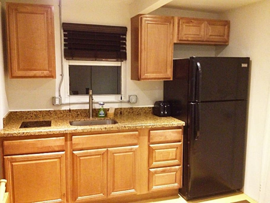 New Kitchen with full fridge, one burner stove top, and a microwave oven.