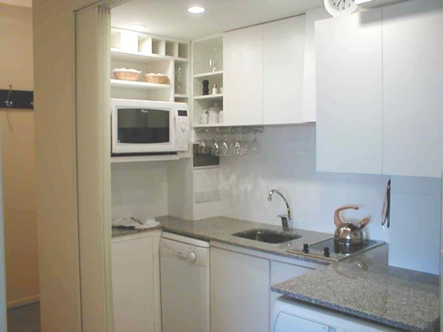 cocina equipada con lavasecaropas y lavavajillas, microondas.