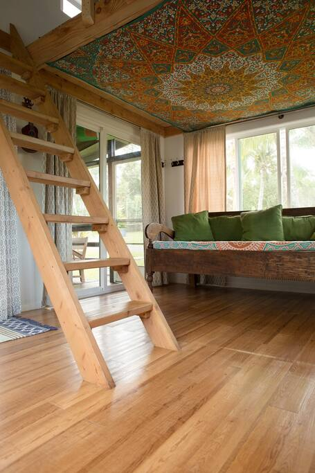 Ladder to sleeping loft with a king bed.