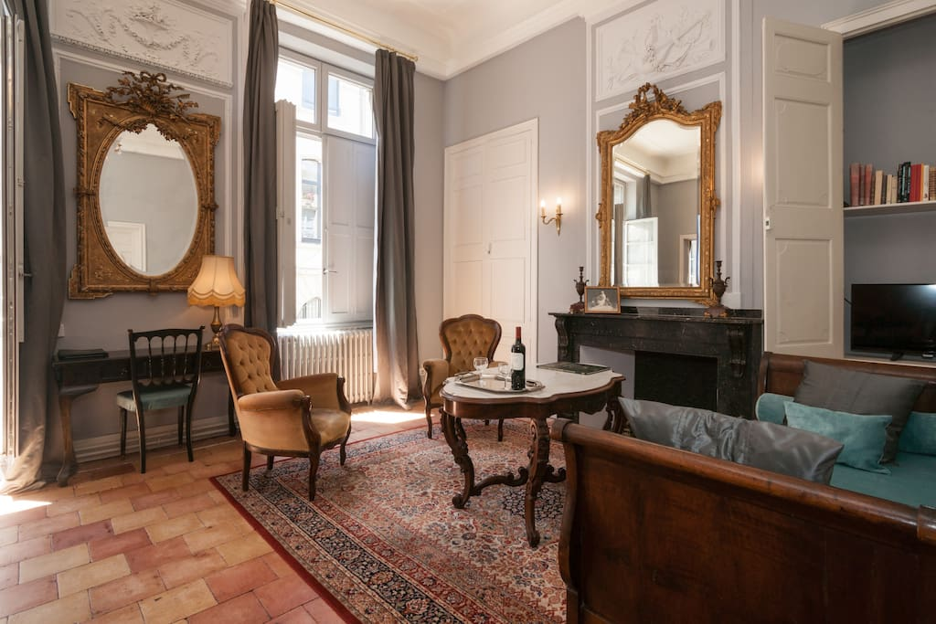 Luxurious living room in French apartment with grey walls, gold ornate mirrors, and Versailles palatial style. #french #apartment #Paris #luxury #vacationrental