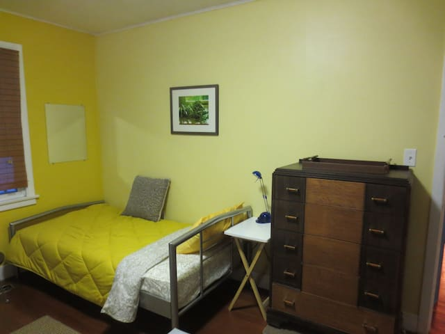 The second twin bed with electric plug, light close by. The head faces the door for auspicious Feng Shui