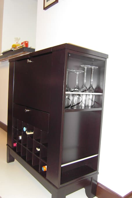 Mini bar in the dining room with wine glasses.
