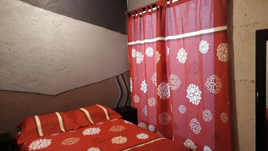 Recamara principal con dos burós cama matrimonial, closet y maletero, lámpara, plancha y mueble con espejo, para accesorios varios.