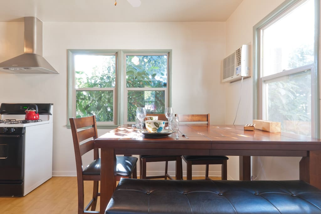 counter height dining room table, leather bench and counter height chair/stools. avocado tree practically reaching inside the kitchen!