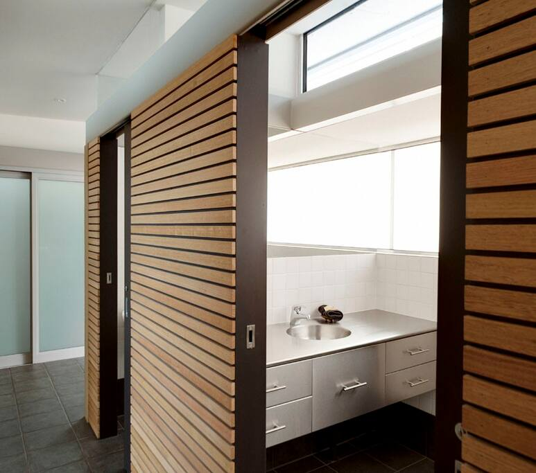 A peek view into the contemporary bathroom from the passage.