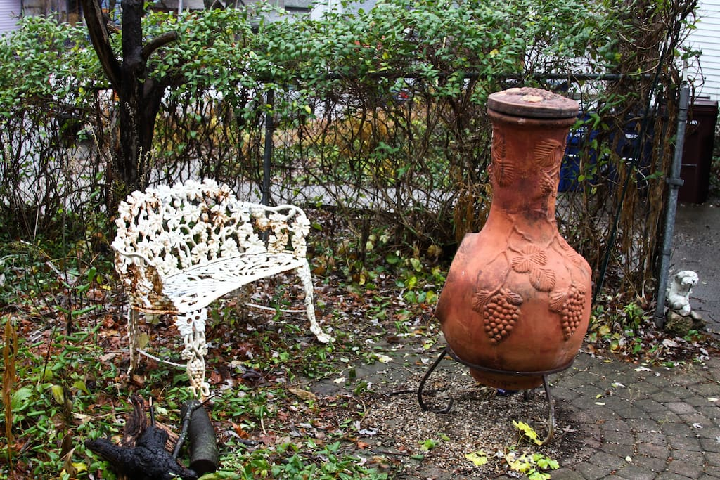 Vintage garden bench and chiminea make for cozy seating on cool evenings