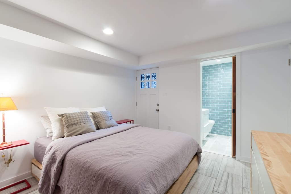 Queen bedroom with hidden closet and drawers and TV