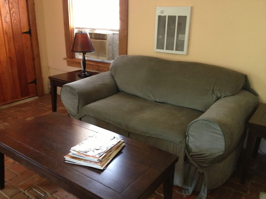 Comfortable love seat with nice assortment of magazines. HVAC is window ac/fan or wall heater/oil heater