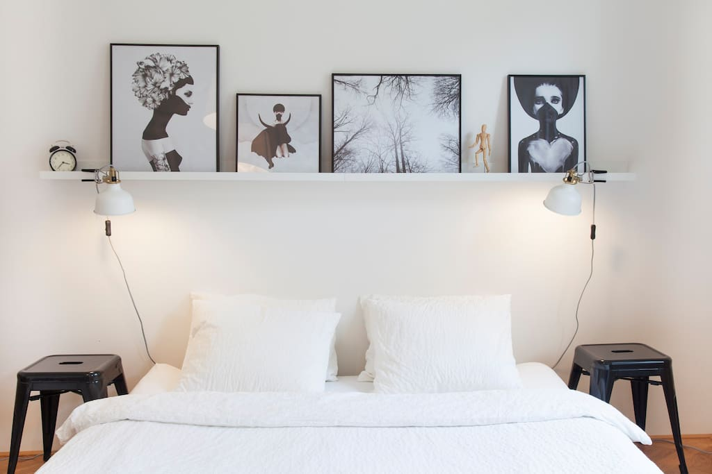Cozy stylish bedroom with (what else) pictures and reading lamps ;)