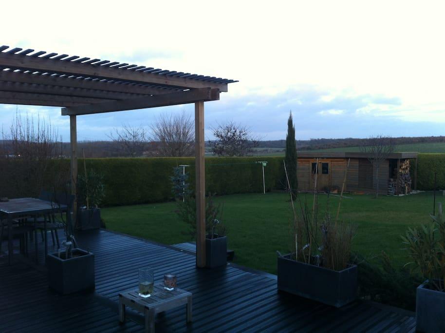 Terrasse en bois et pergolas avec vue sur la plaine.