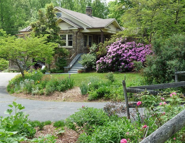 Beautiful gardens surround the home. Also note the off-street parking.