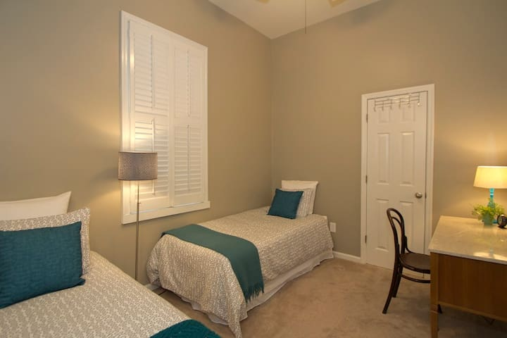 This bedroom has two twin beds, a work desk and an iron / ironing board in the closet.