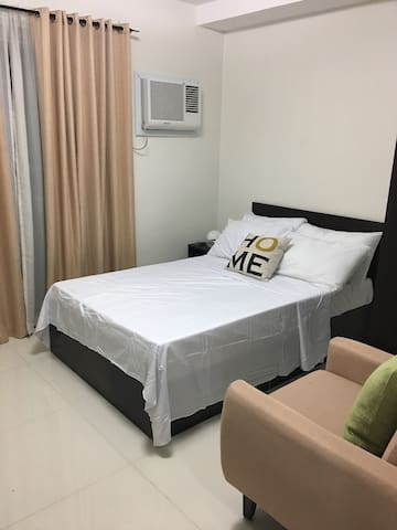 * airconditioning unit * curtains * bed with pillows and bedsheets * upholstered accent chair