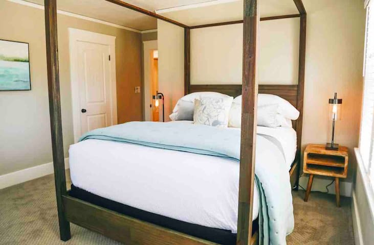 A wooden canopy bed completes another queen bedroom