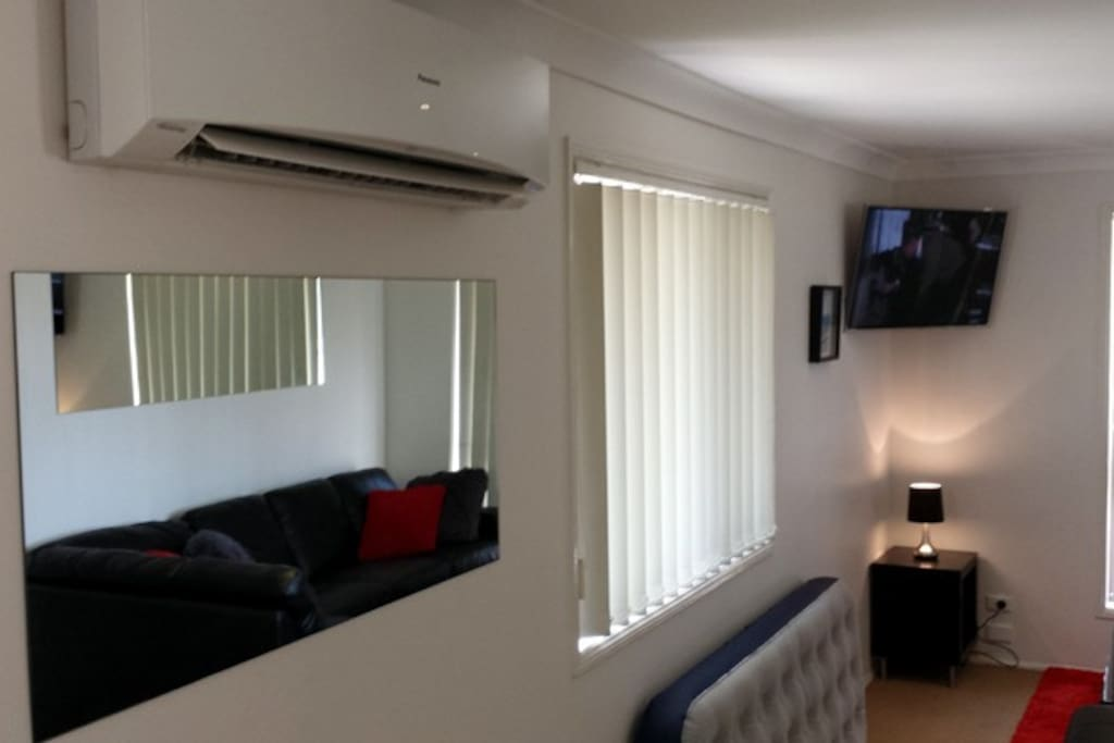 Air conditioner, vertical blinds, wall mounted smart TV.