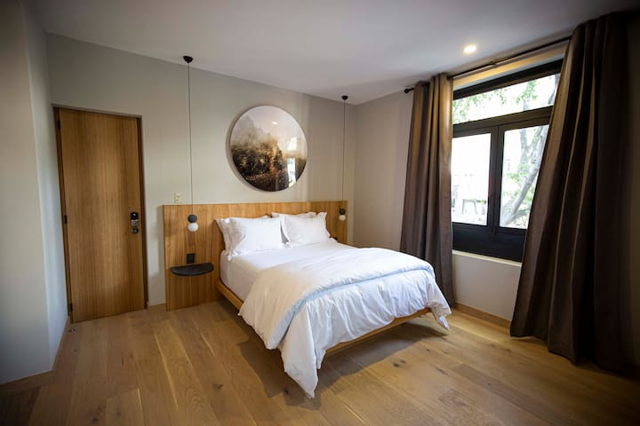 """""""Don Goyo"""", one of the modern suites at Recinto Roma, offers a mix of cosmopolitan design with a twist of Mexican style like the use of volcanic stone, hardwood floors, contemporary artwork and custom furniture."""