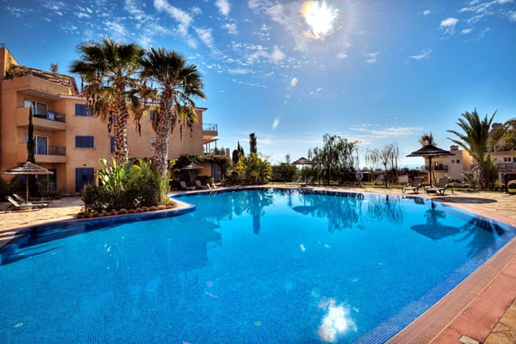 Large communal pool with sun loungers - perfect for relaxing and sunbathing.