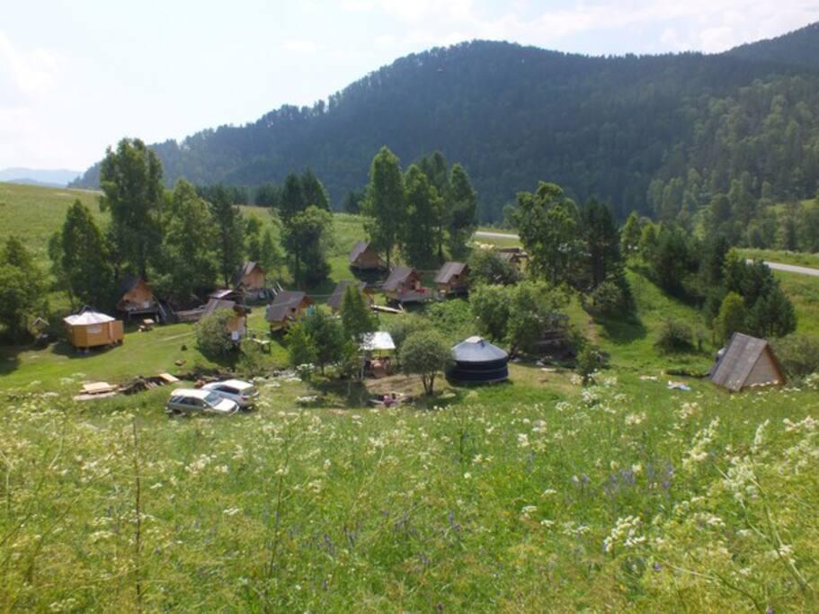 По центру усадьбы протекает горный ручей, кругом горы.