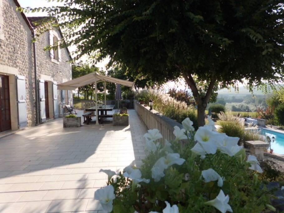 Eén van de grote terrassen . Dit terras kijkt uit over het zwembad, de tuin en het uitzicht