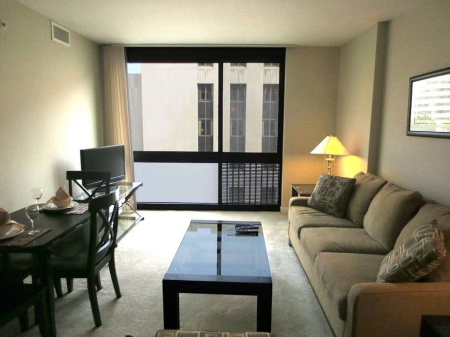 The Living Room features a sofa, arm chair, pullout bed, work desk with chair, flat panel LCD TV with cable channels, DVD player, stereo CD system and floor-to-ceiling windows.
