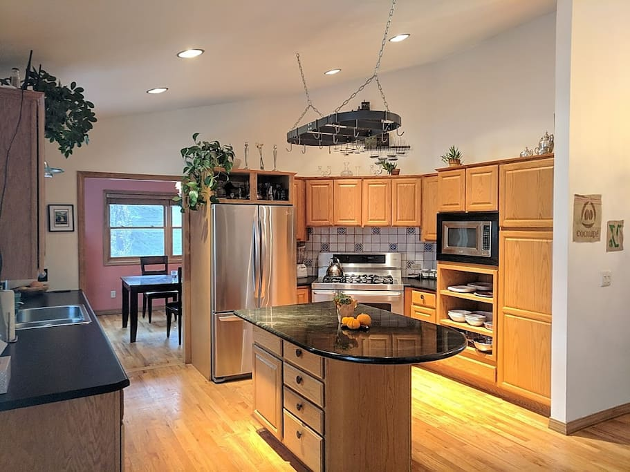 Full kitchen with island, gas range, and dining room beyond