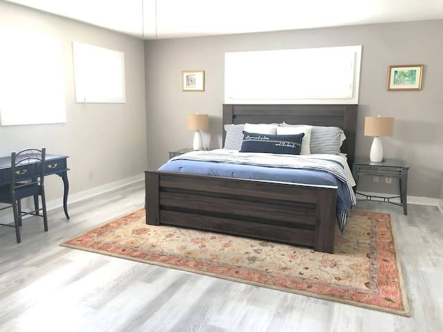 Master bedroom with king bed, walk in closet, desk, smart tv and a futon.