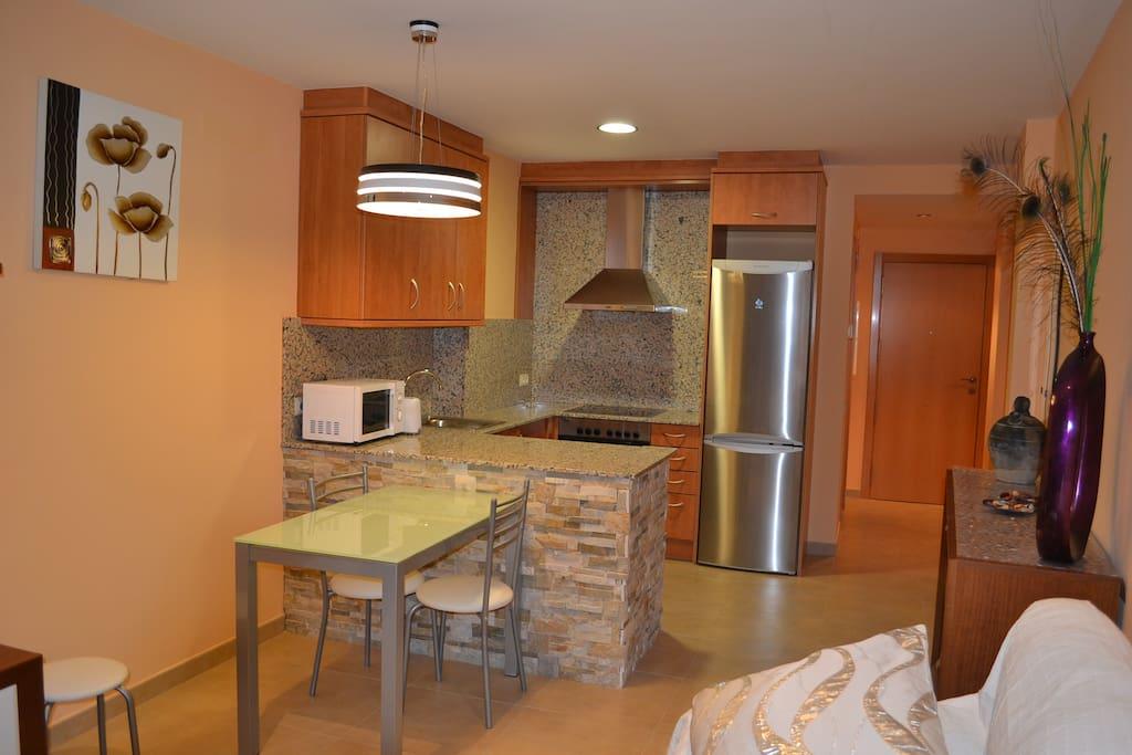 Cocina equipada con enseres de cocina y lavadora.