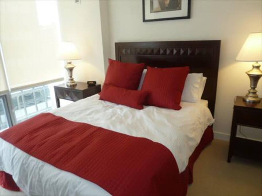 Master Bedroom with Queen Bed, en-suite full bathroom, walk-in closet, and floor-to-ceiling window with city views.