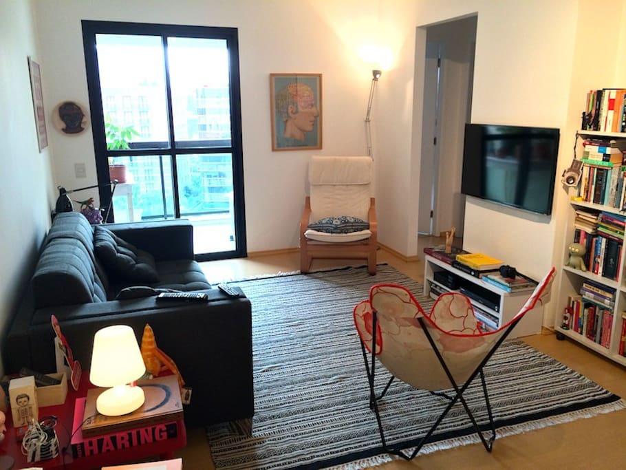 Vista geral da sala de estar com TV LCD 42' e varanda ao fundo