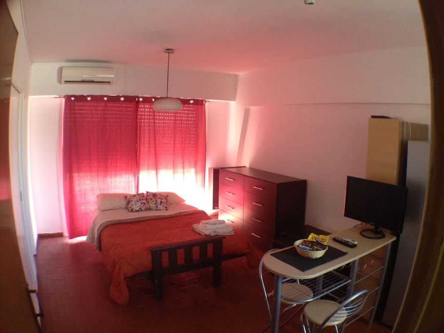 First view as you get in: AC, bed, big drawers, short table, breakfast table and LED TV