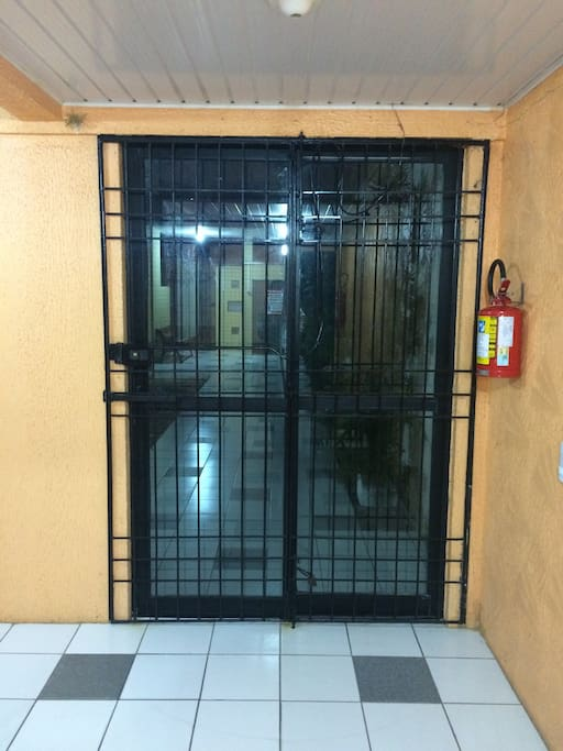 Visão da porta que dá saída do prédio com os portões que garantem a segurança do prédio.
