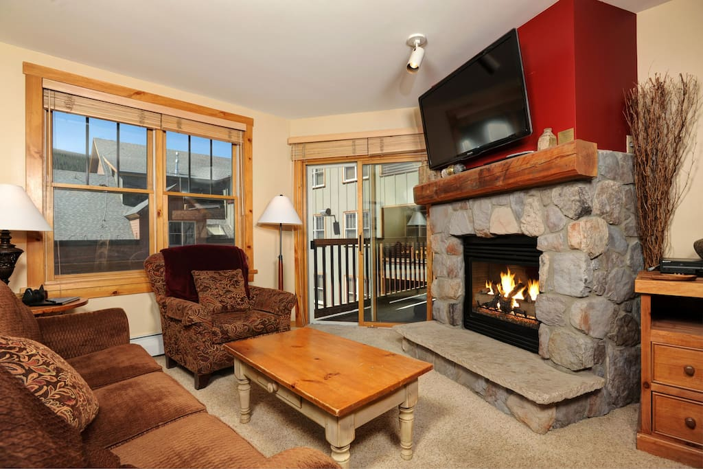 Relax in the luxurious living area, complete with natural stone gas fireplace