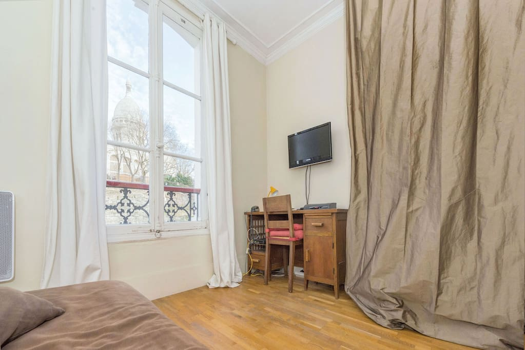 You can see Sacré Cœur through the window! The wardrobe and bookshelf are hidden behind the curtain. The flat screen tv facing the sofa bed and wifi.